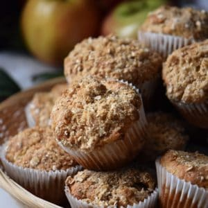 Apple muffins with crumble topping in a wicker basket.