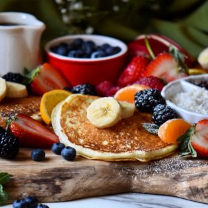 Buttermilk pancakes on a pancake board, surrounded by fruits.