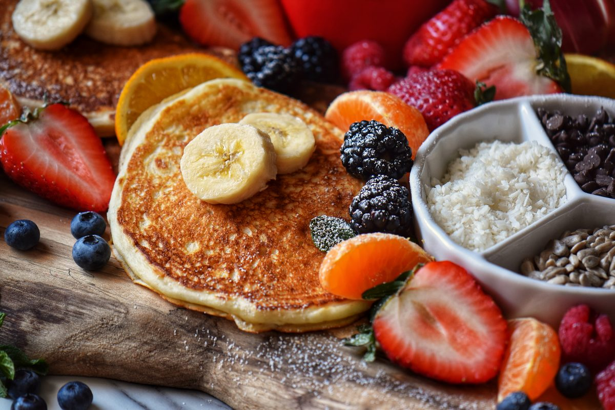 A breakfast board with pancakes, fruit and a variety of toppings.