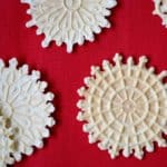 Pizzelle scattered on a red background.