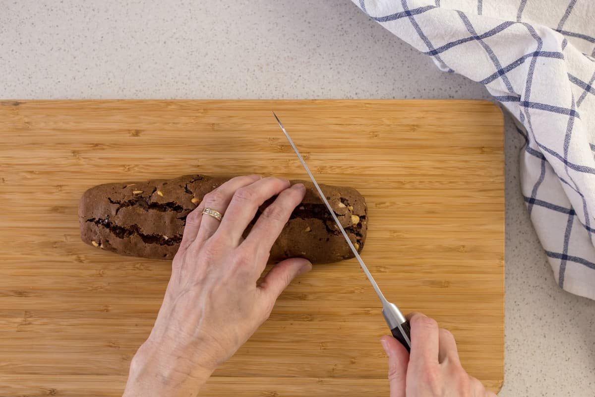 A biscotti log is in the process of being sliced.