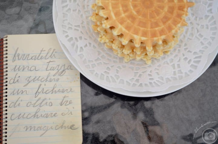 A little booklet with hand written ingredients shown next to a plate of pizzelle de la nonna