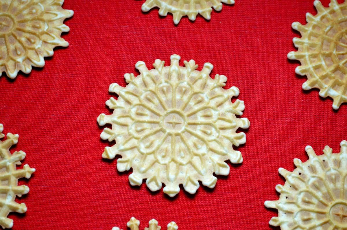 Pizzelle della nonna are shown on a red tablecloth.