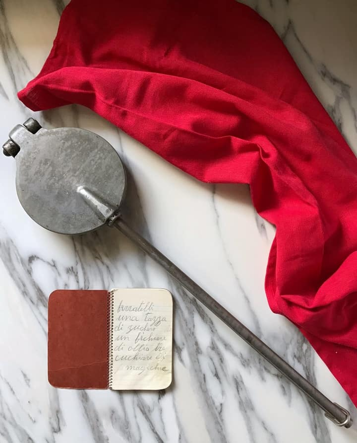 A little booklet with hand written ingredients shown next to a an old pizzelle iron.