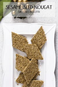 Pieces of sesame seed nougat on a white serving platter.