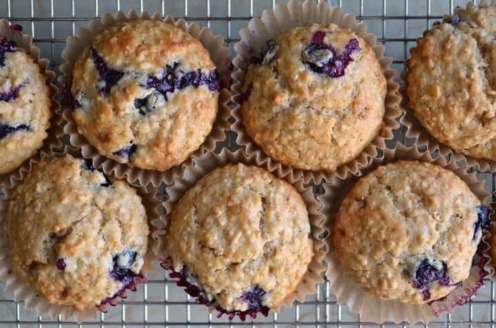 A few blueberry muffins on a cooling rack.