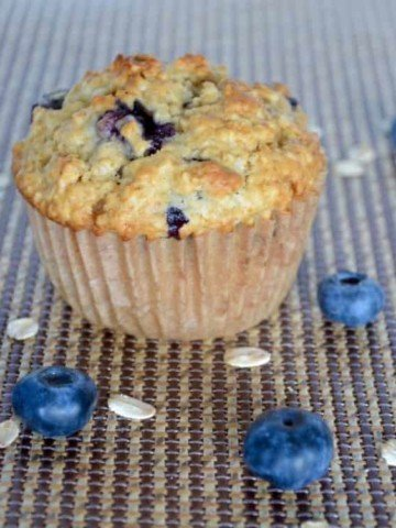 A blueberry muffin surrounded by blueberries and oats.