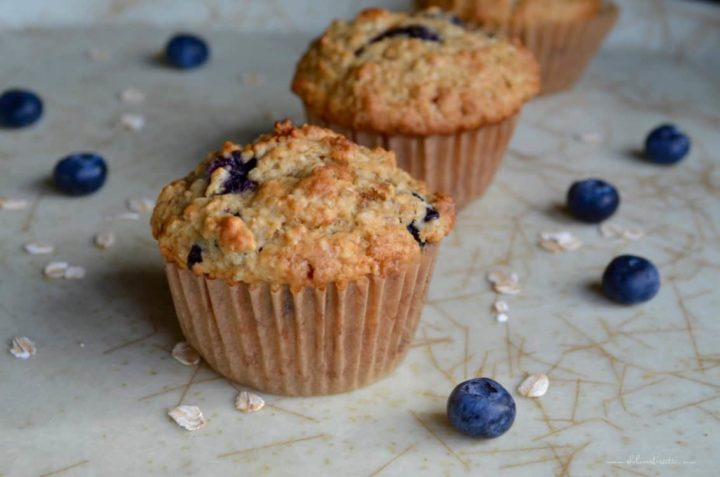 A few Healthy Blueberry Oat Muffins on a tray surrounded by fresh blueberries.
