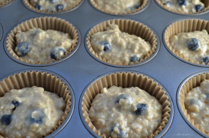 A muffin tin filled with blueberry muffin dough ready to be baked.