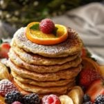 Pancakes surrounded by fresh fruit and dusted with icing sugar.