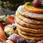 A stack of Oatmeal Pancakes surrounded by fresh fruit.