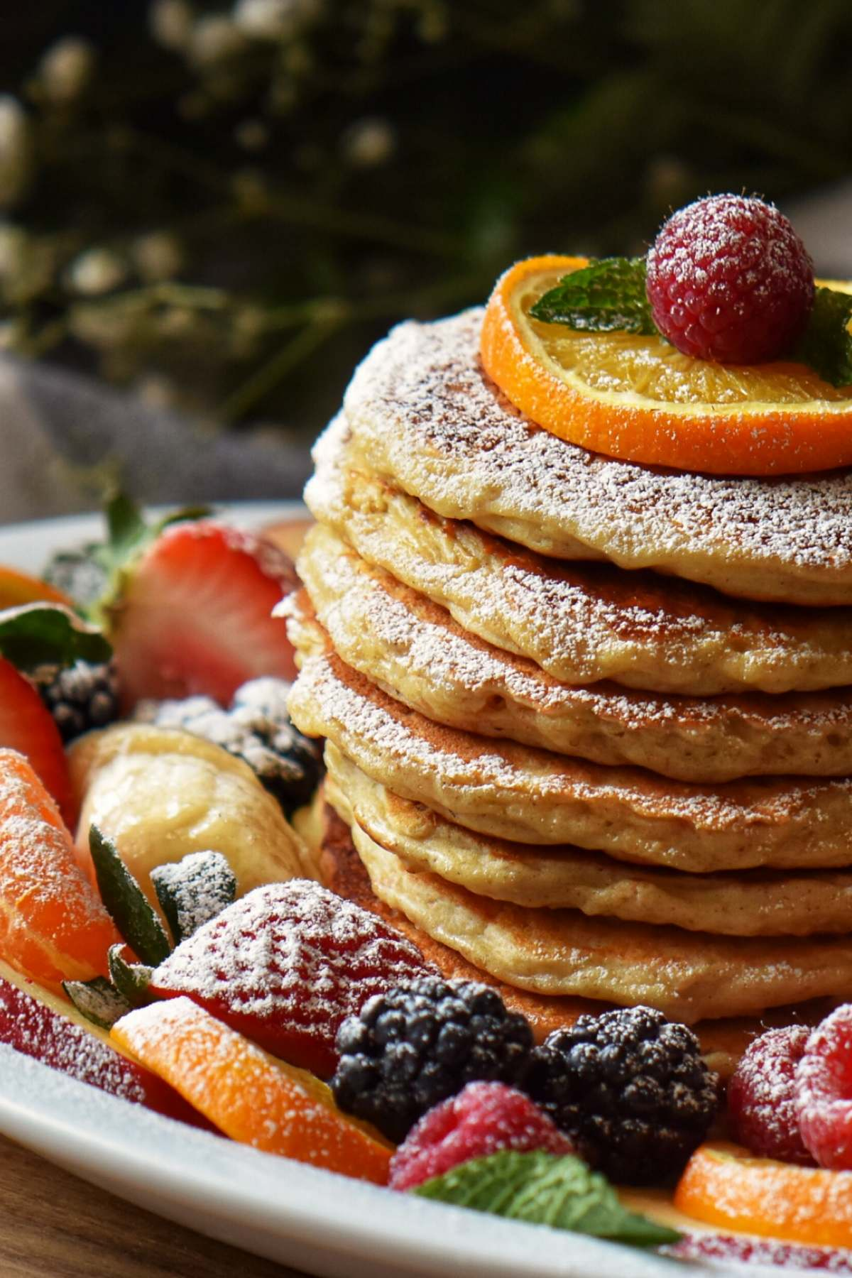 A stack of oatmeal pancakes dusted with icing sugar, garnished with a slice of orange and a raspberry.