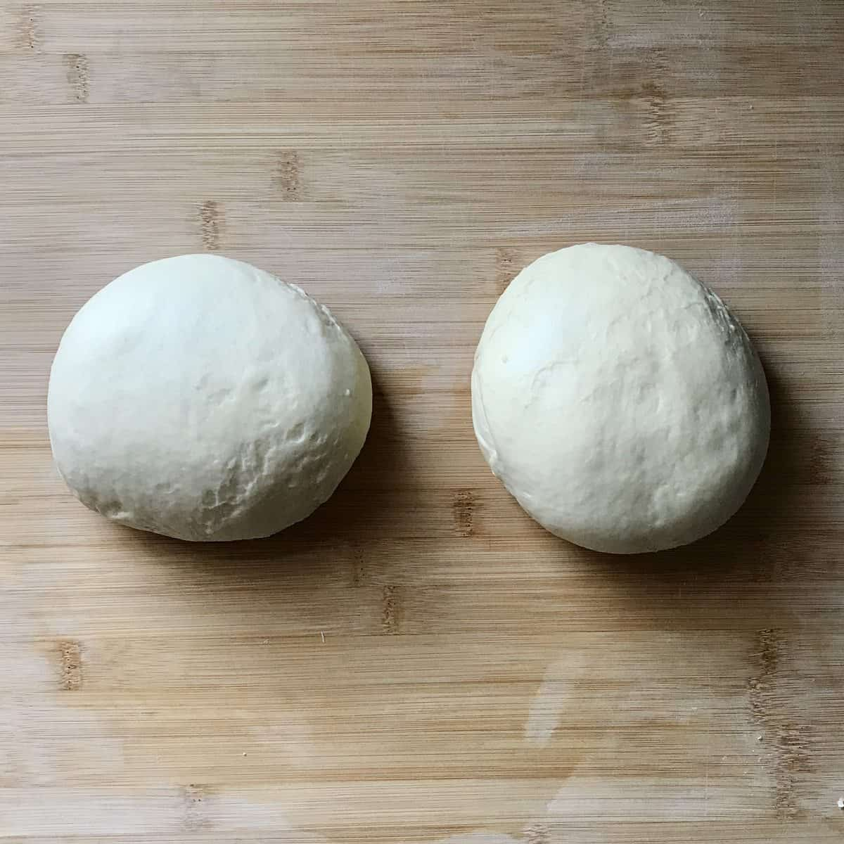 Two balls of dough on a wooden board.