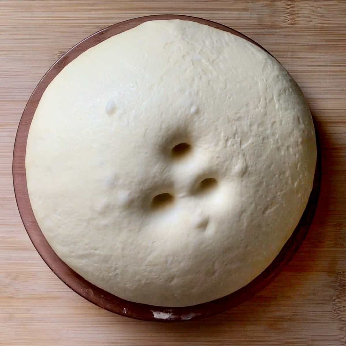 Proofed dough with finger indentations.