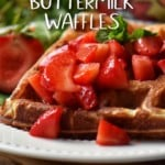 Buttermilk waffles on a white plate topped with macerated strawberries.