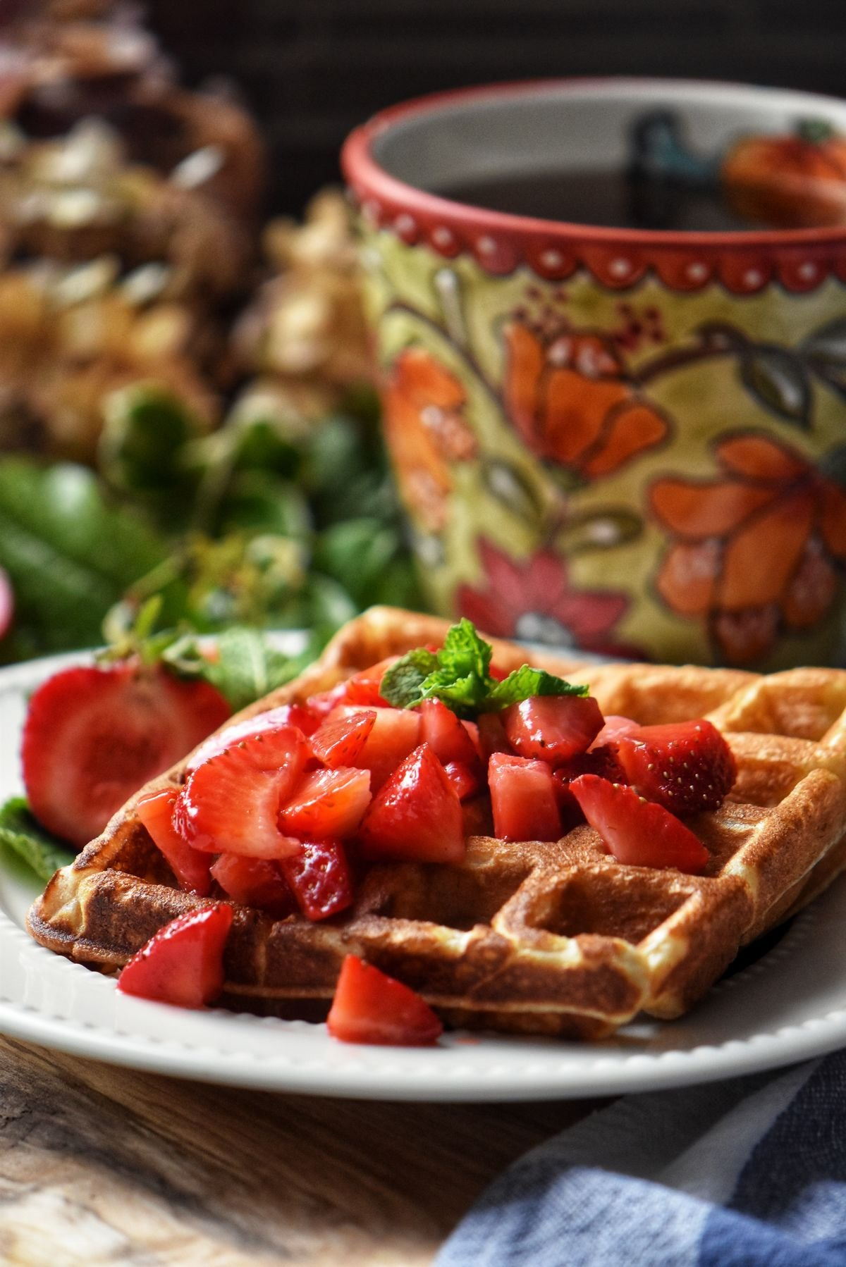 A plate of fluffy buttermilk waffles topped with macerated strawberries.
