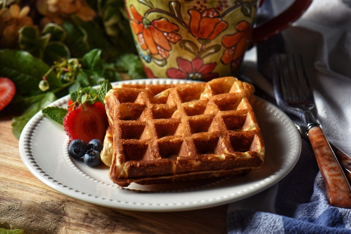 Plain waffles on a white plate with blueberries and strawberries.