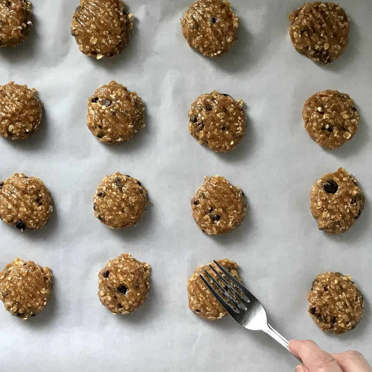 A fork is pressing down on balls of cookie dough.