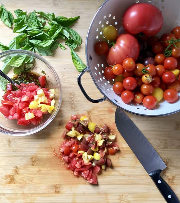 Heirloom cherry tomatoes are chopped into small pieces.