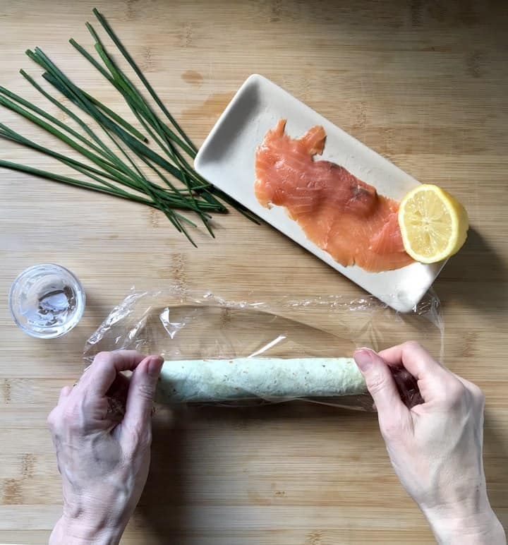 The smoked salmon and cream cheese roll ups are wrapped in a piece of cellophane.