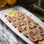 Smoked salmon roll ups garnished with capers and chopped chives.