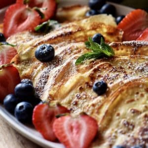 Crepes and berries on a serving platter.