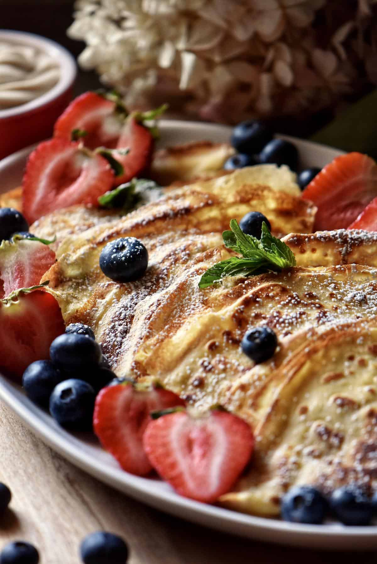 Folded crepes on a white serving platter garnished with fresh berries and icing sugar.