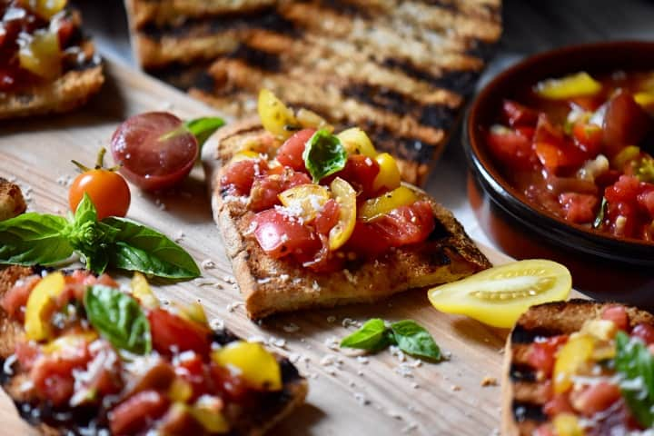 Slices of tomato basil bruschetta on a wooden board, ready to be served as an appetizer.