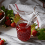 A glass jar of strawberry jam with a spoon surrounded by fresh strawberries.