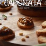 Eggplant caponata on a toasted baguette on a wooden board.