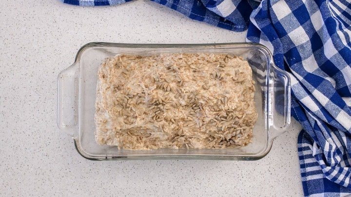 Sunflower seeds can be seen on the honey bread dough in a rectangular pan, about to be baked.