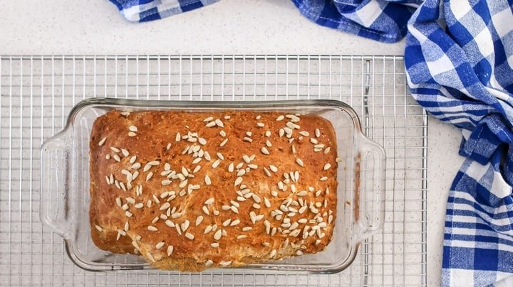 A freshly baked loaf of whole wheat bread on a cooling rack.