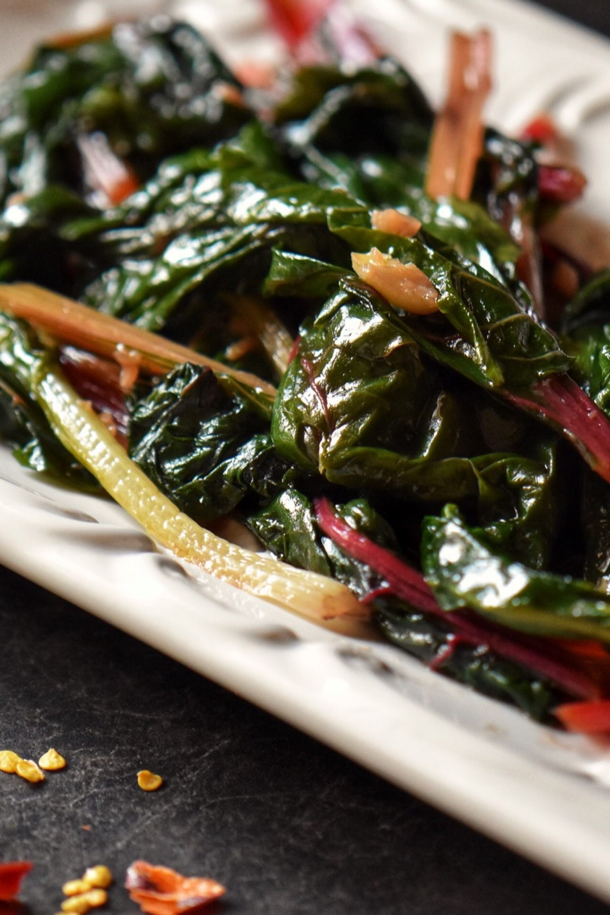 A close up of chard in a white serving dish.