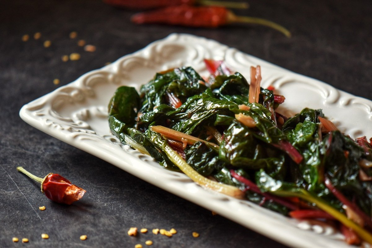 Sauteed chard in a white serving dish.
