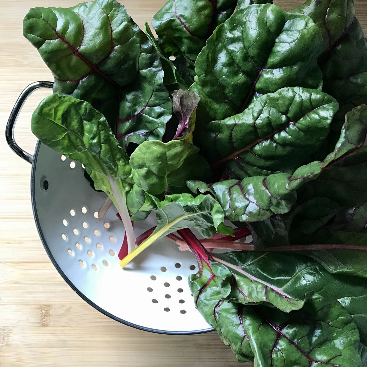 Chard in a white colander.