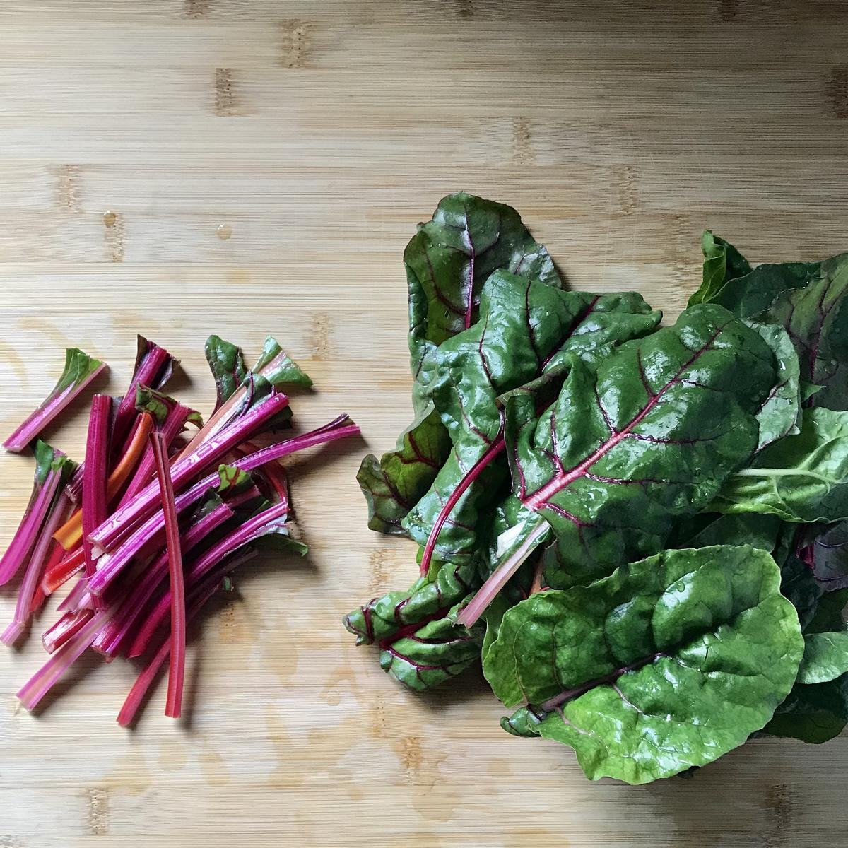 The stems and leaves of rainbow Swiss chard on a wooden board.