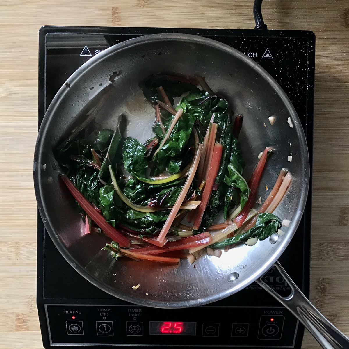Par-boiled Swiss and rainbow chard added to a pan of sauteed garlic.