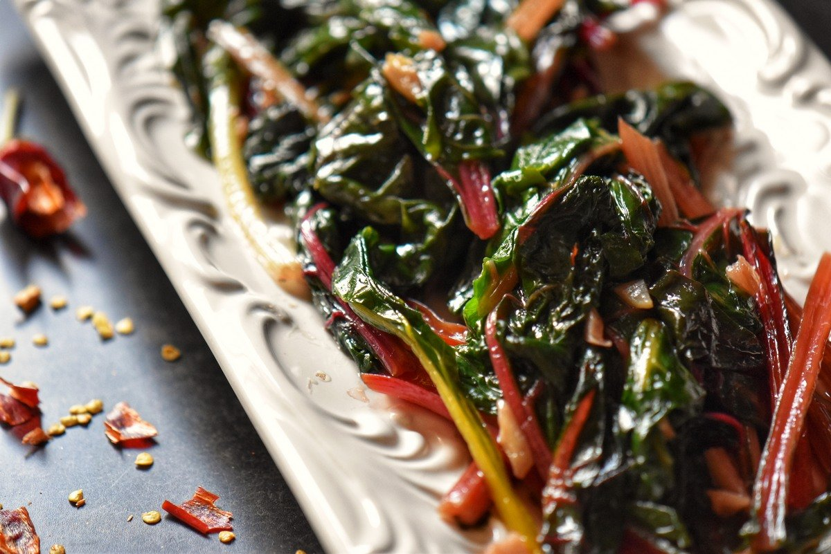 An overhead photo of sauteed Swiss chard in a white serving dish.