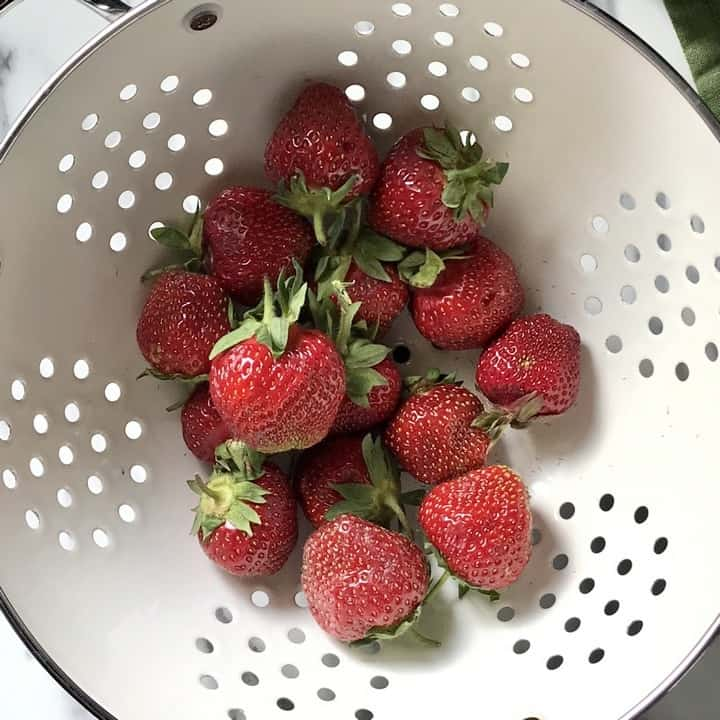 Strawberries in a white colander about to be rinsed.