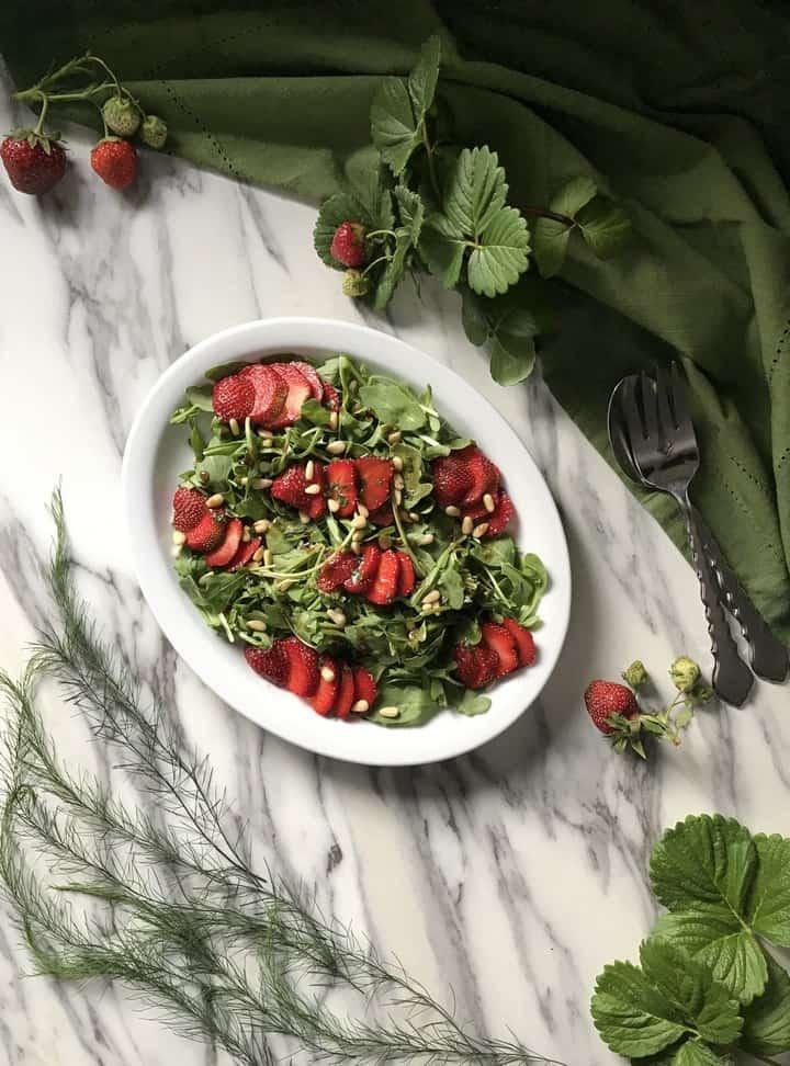 A large white platter of strawberry arugula salad.