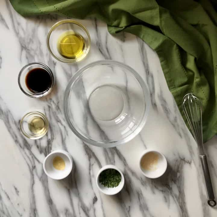Ingredients to make the balsamic vinaigrette in small bowls.