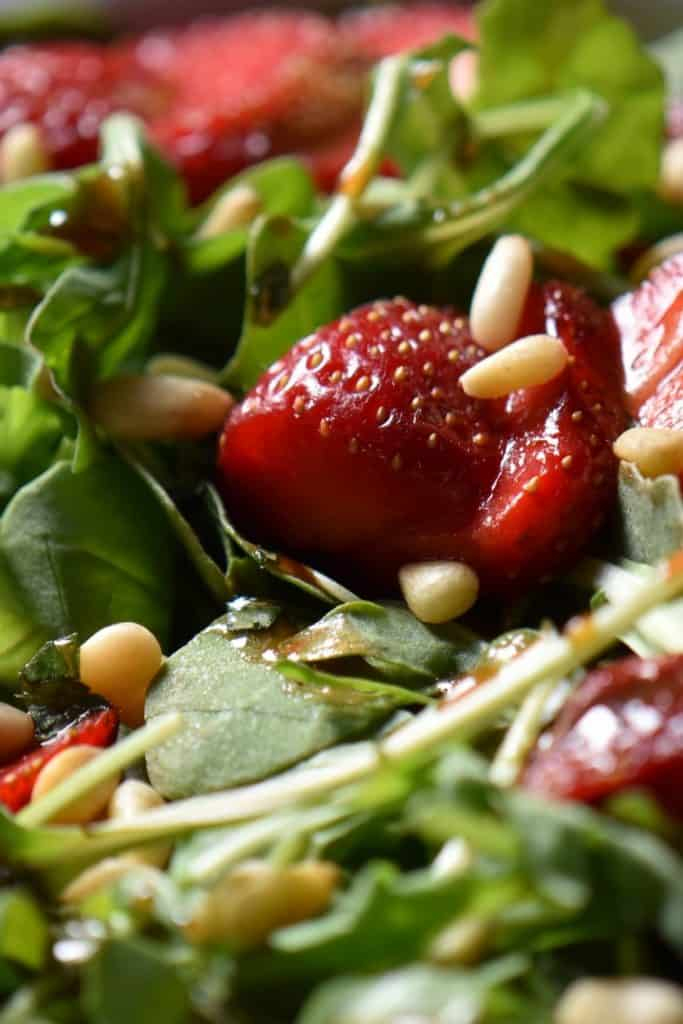 A close up photo of strawberries and arugula.