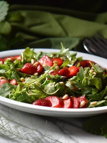 A white oval platter filled with a colorful arugula salad.