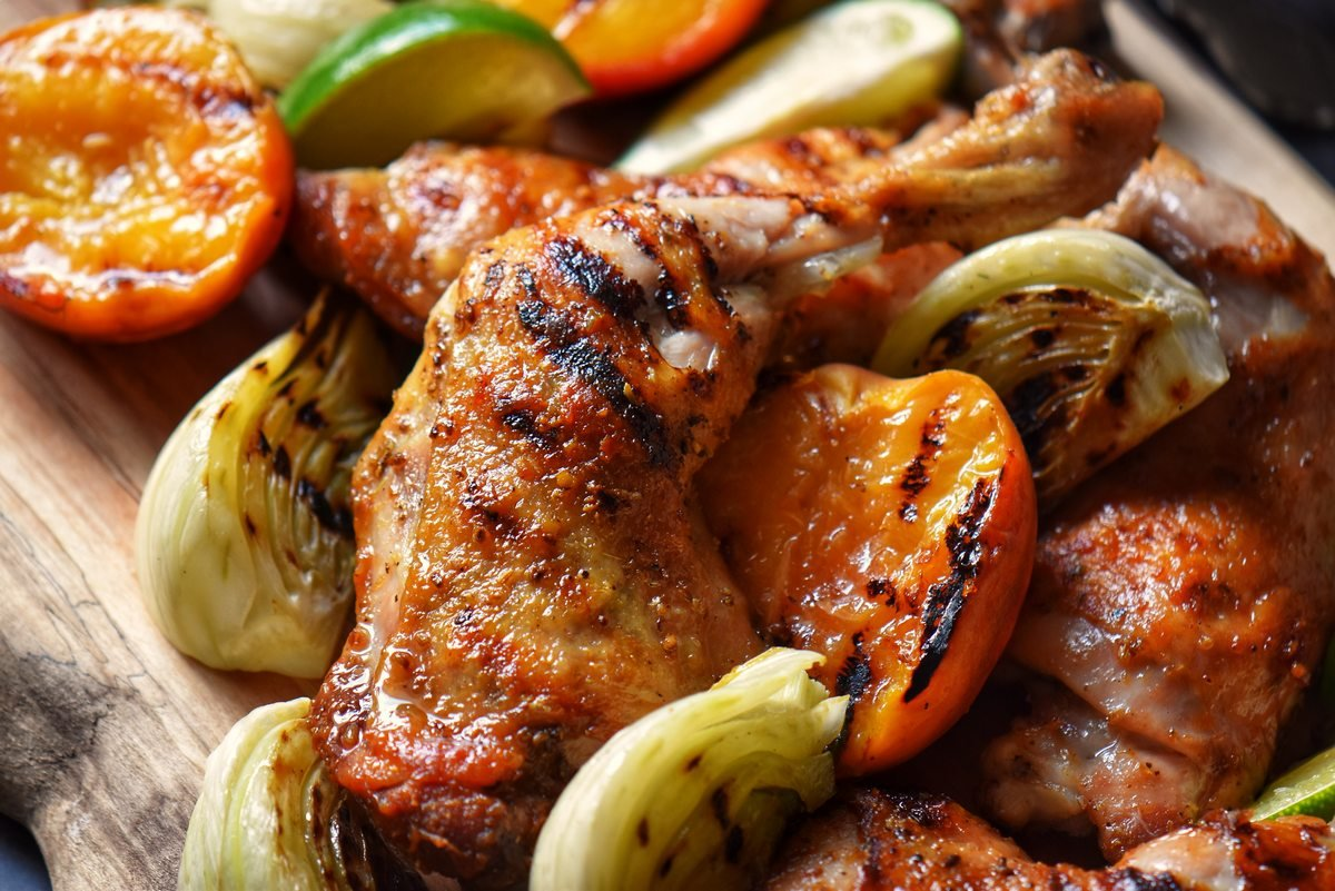 Grilled chicken quarters, fennel and peaches on a wooden board.