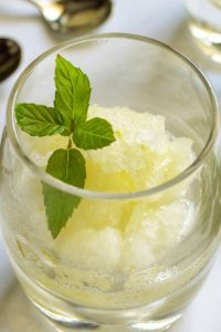Italian Lemon Ice in a glass decorated with a sprig of mint.
