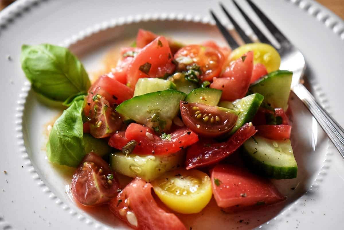 A colorful Tomato Cucumber Salad in a white dish, set alongside a fork.