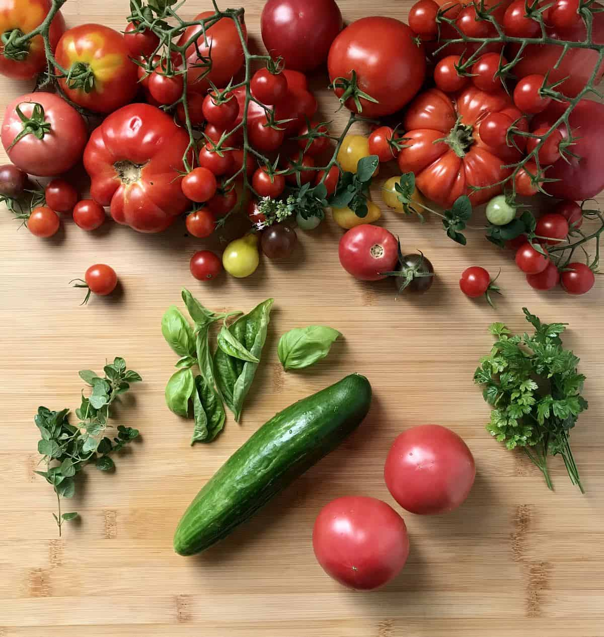 Herbs, one cucumber and lots and lots of different kinds of tomatoes on a wooden board.