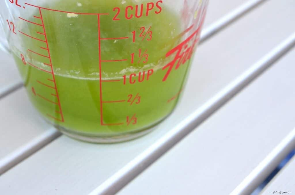 The liquid extracted by squeezing zucchini is collected in a measuring cup.