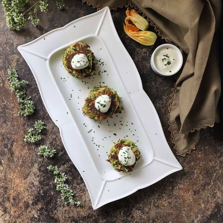 An overhead shot of zucchini fritters on a white plate served with a dollop of yogurt sauce.