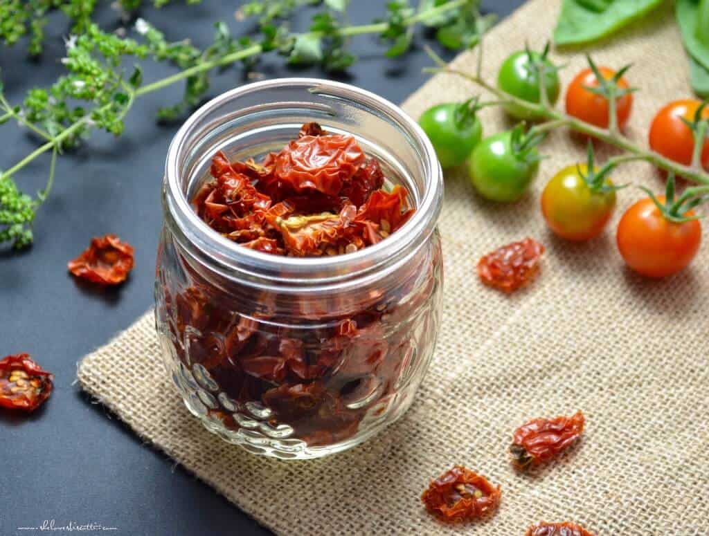 A mason jar filled with dehydrated tomatoes surrounded with fresh cherry tomatoes and oregano.